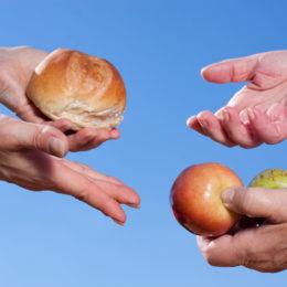 Hände reichen einander Brot und Obst